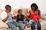 Family at home father and mother with sons ages 3, and 1 year old sitting on couch in living room playing clapping game