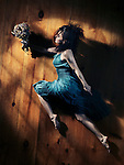 Young woman in a blue dress with a bouquet of wild flowers in a dynamic leap on wooden floor background, abstract artistic portrait in dramatic dim light Image © MaximImages, License at https://www.maximimages.com