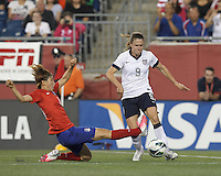 Korea Republic defender Lim Seonjoo (6) slide tackles USWNT midfielder Heather O'Reilly (9). In an international friendly, the U.S. Women's National Team (USWNT) (white/blue) defeated Korea Republic (South Korea) (red/blue), 4-1, at Gillette Stadium on June 15, 2013.