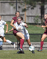 Boston College defender McKenzie Meehan (22) brings the ball forward but encounters Virginia Tech defender Danielle King (8).Virginia Tech (maroon) defeated Boston College (white), 1-0, at Newton Soccer Field, on September 22, 2013.