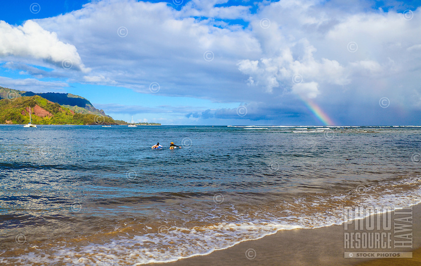 A rainbow graces the day as surfers paddle towards other more distant surfers in Hanalei Bay, Kaua'i.