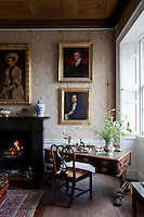 A corner of the nineteenth century gallery, hung with different eras of portraiture, some of which conceal a jib door