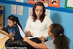 Afterschool homework help program for Headstart graduates Grades K-3 female teacher working with first or second grade student, math activity