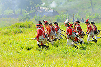 British redcoat soldiers charge the  Continental Army defenses during a Revolutionary War re-enactment at Fort Ticonderoga, New York, USA.