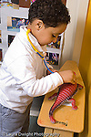 Preschool 3-5 year olds pretend play boy using stethoscope on dinosaur toy vertical
