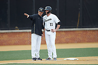 Wake Forest Demon Deacons head coach Tom Walter (16) gives instructions to Shane Muntz (11) during the game against the Sacred Heart Pioneers at David F. Couch Ballpark on February 15, 2019 in  Winston-Salem, North Carolina.  The Demon Deacons defeated the Pioneers 14-1. (Brian Westerholt/Four Seam Images)