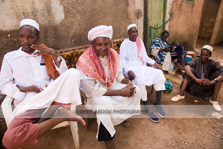 Three devout Muslim men relax in the afternoon sun.  They have traveled from western Burkina Faso to the capital, Ouagadougou, to visit relatives and conduct other business.