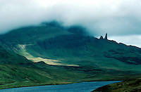 Rock spires rise amidst fog above a green hillside on the Isle of Skye. scenic view, Scottish landscape, formations. Scotland Great Britain Isle of Skye.
