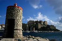 Lighthouse overlooking the port and a fortified citadel in Calvi, Corsica, France.