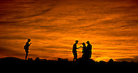 Sunset colors silhouette a cordial interaction between couples at 10,000 feet in Haleakala National Park, Maui.