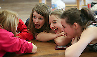 "Friends having fun together.  Drama group for 8-13s run by Yvonne Arnaud Theatre, rehearsing a production of ""Alice"" in a school hall, Guildford, Surrey."
