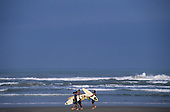 Southern Brazil. Surfer boys walking on the beach with their Malibu surf boards with waves in the sea behind.
