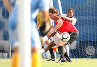 Robert Burnett #22 of Georgetown University pokes the ball past Matt Sanford #6 of Northeastern University during an NCAA match at North Kehoe Field, Georgetown University on September 3 2010 in Washington D.C. Georgetown won 2-1 AET.