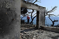 Pictured: A fire fighter assesses the damage in the aftermath of the forest fire which has claimed dozens of lives in the Mati area of Rafina, Greece. Wednesday 25 July 2018<br /> Re: Deaths caused by wild forest fires throughout Greece.