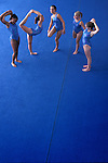 group of five teenage girl gymnasts doing various stretching exercises on large blue mat