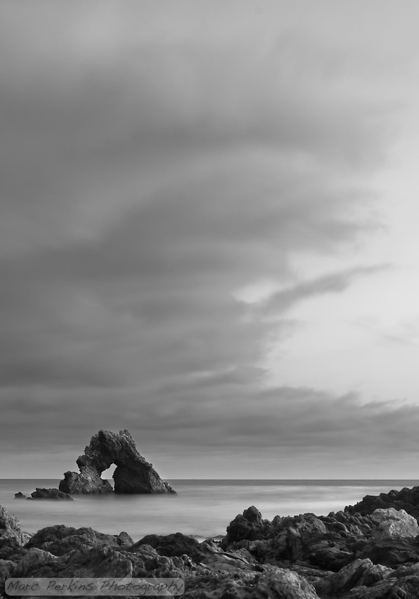 A vertical view of the arch rock offshore at Little Corona after sunset, in black and white using a long exposure to make the ocean water silky smooth.  I love the soft curves of the clouds drifting overhead.