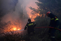 Pictured: Firemen battle with flames at near the village of Kapandriti.<br />