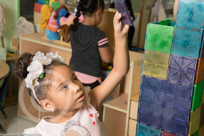 Education Preschool 4 year old girl building tall structure with magnet tile blocks