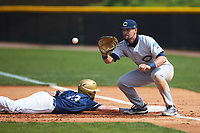 Hunter Shepherd (18) of the Catawba Indians waits for a pick-off throw as Mason Pickard (13) of the Queens Royals dives back into first base during game one of a double-header at Tuckaseegee Dream Fields on March 26, 2021 in Kannapolis, North Carolina. (Brian Westerholt/Four Seam Images)