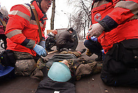 Red Cross Medics and volunteers help a man that has been shot as others use shield to protect from bullets rounds on the battlefield of maidan square.  Kiev, Ukraine