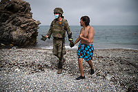 CEUTA, SPAIN ‐ MAY 19: A Spanish soldier shakes hands with a migrant as he leaves the water on the Tarajal beach, after having crossed the border between Morocco and Spain swimming on May 19, 2021 in Ceuta, Spain.  After a diplomatic conflict between Spain and Morocco, thousands of migrants who have taken advantage of the little Moroccan police activity on the border to cross it mainly by swimming, which has caused a migration crisis with the entry of more than 8000 migrants from the African country. (Photo by Joan Amengual/VIEWpress )