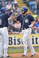 Asheville Tourists first baseman Sean Dwyer (27) is congratulated at home plate by Forrest Wall (7) after hitting a home run during game one of a double header against the Greenville Drive on April 18, 2015 in Asheville, North Carolina. The Tourists defeated the Drive 2-1. (Tony Farlow/Four Seam Images)