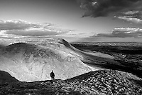 A walker on the summit of Dumgoyne, looking across the Campsie Fells to Glasgow, above Glengoyne, Stirlingshire
