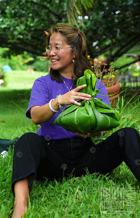 Woman at Kalani Honua retreat center making a Hawaiian hookupu offering out of ti leaves, Big Island