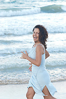 Portrait taken at Kailua beach of beautiful curly haired woman at age 50 wearing soft blue dress