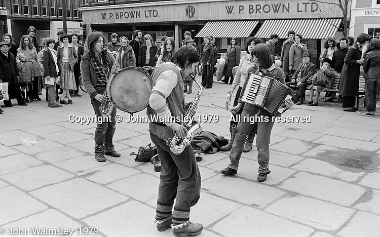 The York Street Band playing in York, March 1979.  Dena Attar on saxophone, Sarah Kemp on washboard (hidden), then the three members of the YSB: Ros Davies (saxophone), Sarha Moore (tambourine) hidden and Anthea Gomez (accordian).  Sarha Moore and Ros Davies went on to play in The Bollywood Band, and Ros also joined the Grand Union Band, in London.  Anthea Gomez went on to write and play music for the theatre and then BBC Drama before changing direction.