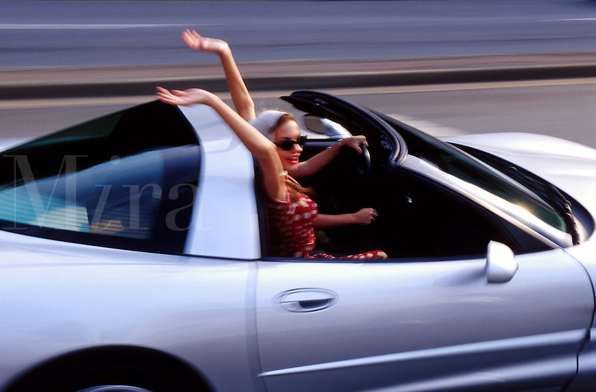 Blurred motion image of a smiling young woman with her arms in the air as she rides in a silver Corvette.