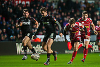 Friday 03 January 2014<br /> Pictured:Kristian Phillips of the Ospreys Kicks the ball past the Scarlets defence<br /> Re: Ospreys v Scarlets, Rabo Direct Pro 12 match at the Liberty Stadium Swansea, Wales