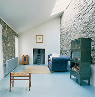 A simply furnished sitting room is decorated in a palette of blues and neutrals, which creates a cool, calm mood whilst the overhead skylights allow light into the room. The rough-hewn stone walls and sloping ceiling are a reminder of the orginal out-building before being converted into a holiday home.