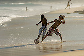 Rio de Janeiro, Brazil. Ipanema Beach; kids playing football in the sea.