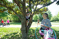 Lark Johnson, 6, climbs a magnolia tree Thursday June 3, 2021 at Gulley Park in Fayetteville. Lark was at the park with her babysitter, Lexi Petty of Fayetteville (right). Visit nwaonline.com/2100604Daily/ and nwadg.com/photo. (NWA Democrat-Gazette/J.T. Wampler)