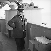 Winston Churchill wearing leather ear defenders watches gunnery practice on board HMS RENOWN whilst he was returning from Canada, September 1943.