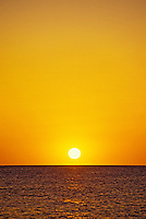 The setting sun casts a rich golden glow  in the cloudless sky and over the horizon of the calm Pacific ocean.