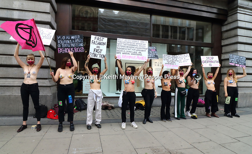 Topless activists wearing an X and Extinction Rebellion logos to cover her nipples holding placards during the Redress the Injustice protest outside the H&M store in Oxford Street, opposing the fashion industry's many human, animal and environmental injustices claiming that, it currently produces around 10% of all humanity's carbon emissions. Its emissions are predicted to increase by around 50% by 2030. London September 9th 2020<br /> <br /> Photo by Keith Mayhew