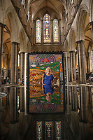 BNPS.co.uk (01202) 558833<br /> Pic: ZacharyCulpin/BNPS<br /> <br /> 8 million stitches, 1 Holy Exhibition<br /> <br /> Pictured: Reflected in the Cathedral font, artist Jacqui Parkinson with an embroidery entitled, 'Goodbye to Eden'<br /> <br /> Twelve large embroidered panels fashioned from eight million stitches which tell the story of 'the Creation' have gone on display at Salisbury Cathedral.<br /> <br /> The panels, which measure up to 8ft by 11ft, are made from silk, hand-dyed materials, gold leaf and metallic leathers.<br /> <br /> They have been created by Devon-based textile artist Jacqui Parkinson who has dedicated three years to the solo project.<br /> <br /> The panels are inspired by the poetic verses of Genesis, the first book in the Bible, and include depictions of the Garden of Eden.