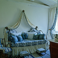 A wrought-iron daybed is decorated in a variety of blue and white fabrics