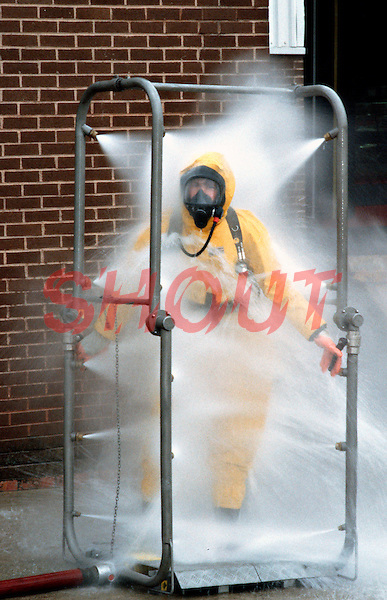 Firefighters wearing breathing apparatus and chemical protection suits showering to remove any chemicals on their suits after attending a chemical spillage in a large factory. This image may only be used to portray the subject in a positive manner..©shoutpictures.com..john@shoutpictures.com
