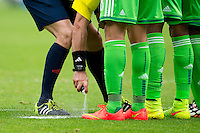 The referee sprays vanishing spray to mark a freekick