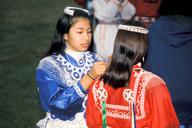 Young Chickasaw lady dancers dressed in traditional clothing  with beadwork attend to last minute touches