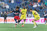 FOXBOROUGH, MA - AUGUST 4: Tajon Buchanan #17 of New England Revolution takes a shot as Dave Romney #4 of Nashville SC defends during a game between Nashville SC and New England Revolution at Gillette Stadium on August 4, 2021 in Foxborough, Massachusetts.
