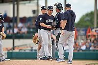 New York Yankees starting pitcher Chance Adams (43) prepares to hand the ball to manager Aaron Boone as he makes a pitching change as first baseman Luke Voit (45) and catcher Austin Romine (28) look on during a Grapefruit League Spring Training game against the Detroit Tigers on February 27, 2019 at Publix Field at Joker Marchant Stadium in Lakeland, Florida.  Yankees defeated the Tigers 10-4 as the game was called after the sixth inning due to rain.  (Mike Janes/Four Seam Images)