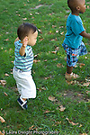 12 month old and 15 month old toddler boys walking outside on grass seen from the side vertical