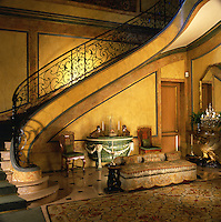 The walls of the entrance hall of the Duke and Duchess of Windor's Paris home are marbleised and the large curved staircase has an ornate wrought-iron balustrade