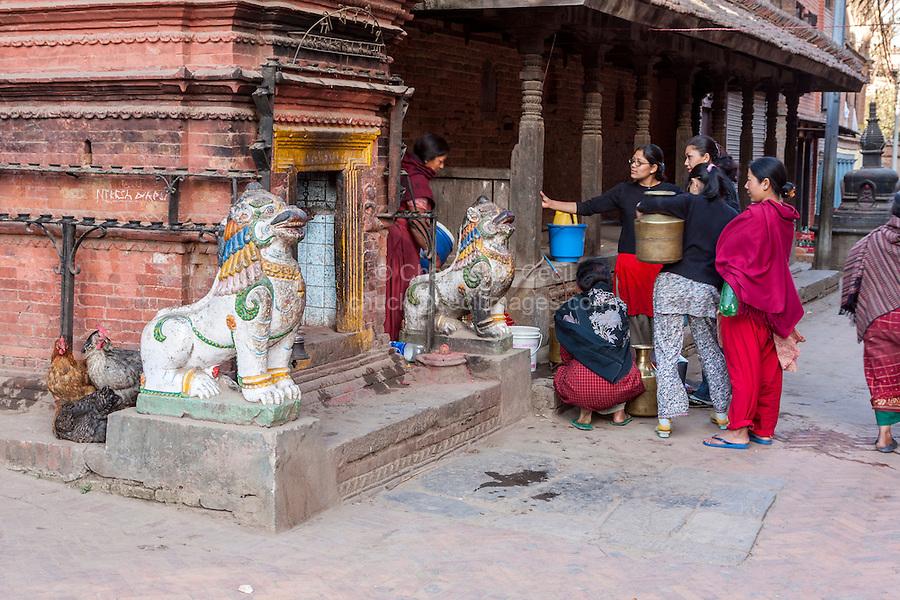 Bhaktapur, Nepal.  Women Waiting their Turn at Public water Tap.  Lions Guard a  Neighborhood Hindu Shrine on Left.