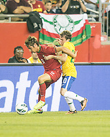 Portugal defender Fabio Coentrao (5) holds off Brazil midfielder Bernard (20).  In an International friendly match Brazil defeated Portugal, 3-1, at Gillette Stadium on Sep 10, 2013.