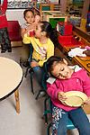 Education Preschool 4-5 year olds group of children pretending to drive using plates as steering wheels